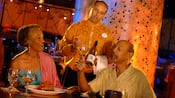 A couple laughs as they drink near food and 2 kitchen staff members