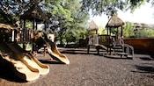 Un patio de juegos empedrado con toboganes y plataformas bajo los techos de paja de Disney's Animal Kingdom Lodge