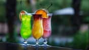 Three specialty drinks sitting on a wooden bar