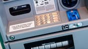 An ATM with a sign that states the machine offers audio assistance for the visually impaired