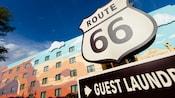 """Letrero de """"Lavandería para Huéspedes"""" debajo de un letrero con forma de escudo de 'Route 66'"""