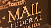 Close-up of the front of a bronze U.S. Mail chute