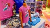 Camiseta da Ariel em um torso de manequim em uma área de exibição de mercadorias de um minimercado