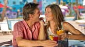 Una pareja sonriente sosteniendo bebidas junto a una piscina