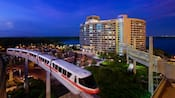 The monorail in motion, passing by Bay Lake Tower in the evening