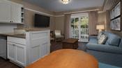 Une cuisine et une table à manger donnant sur un coin salon avec une télévision, 2chaises, canapé , table basse et balcon
