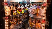Assorted plush keychains from Mickey Mouse to Winnie the Pooh on a hanging display