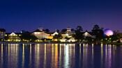 The night lights of Disney's Beach Club Resort with purple glow of Epcot's Spaceship Earth