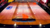 View of an air hockey table with 2 orange paddles