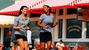 2 mujeres disfrutan de correr mientras pasan frente a una tienda con un toldo a rayas rojas y blancas