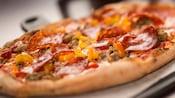 Una pizza cubierta con pimientos, salchicha y pepperoni
