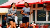 2 women enjoying a jog while passing a storefront with a red and white striped awning