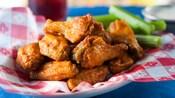 Una pila de alitas con salsa Buffalo en un plato con bastones de apio