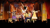 A group of performers in pioneer clothing pose on a stage with a sign that reads Pioneer Hall Players
