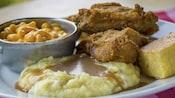 Poulet frit, pain de maïs, macaroni au fromage et purée de pommes de terre recouverts de sauce dans une assiette