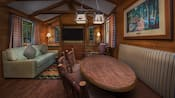 A rustic dining table in front of a lodge chair, a sofa with throw pillows and a flat screen TV