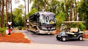 A luxury R V and a golf cart provide comfort in the campground surroundings