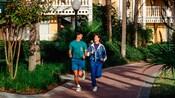 Um homem e uma mulher correndo em um caminho de um Hotel Resort Disney
