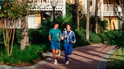 A man and woman jogging on a path of a Disney Resort hotel