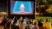 Un groupe de visiteurs se rassemble sur la pelouse pour regarder la projection d'un film Disney