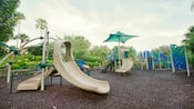 Jardín de juegos con escalones, plataformas y tobogán para niños pequeños.
