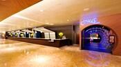 Un largo mostrador de check-in de Disney's Contemporary Resort junto a la entrada del restaurante Wave