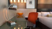 A glass-top desk with lamp and office chair next to a bed at Disney's Contemporary Resort