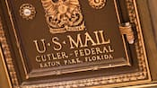 Front of a bronze U.S. Mail chute