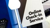 Un letrero, sobresaliendo de una pared, que dice 'Online Check-In Service' (Servicio de check-in en línea)