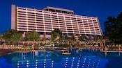 Vue du bord de la piscine sur l'arrière du Disney's Contemporary Resort, éclairé la nuit