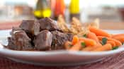 A close-up of beef pot roast, carrots and toast points on a plate
