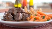 Primer plano de un plato con guiso de carne, zanahorias y tostadas