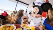 Una familia comiendo en una mesa con comida de desayuno mientras Mickey Mouse habla con una niña