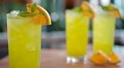 3bebidas, ornamentadas com uma fatia de laranja e um ramo de hortelã