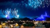 Fuegos artificiales estallan en el cielo sobre Space Mountain y Cinderella Castle