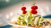 2pedaços de alface americana apresentado com cebolinha, molho ranch, pedaços de bacon e tomate-cereja