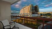 Le balcon d'un hôtel avec une chaise et une table surplombant un trottoir menant au Disney's Contemporary Resort