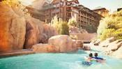 Un père et son fils nagent bras dessus bras dessous dans la piscine Copper Creek Springs