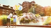 A young girl holds 3 Disney themed balloons as her older brother taps her back and points to the Resort's accommodations
