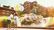 Una niña pequeña sostiene 3globos con temática de Disney mientras su hermano mayor le da una palmada en la espalda y señala el hotel