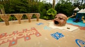 Vegetation surrounds a Mayan inspired playground, with swings, a jungle gym and a sandbox with a large hollow statue of a Mayan head