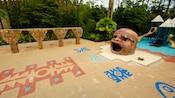 Vegetação em volta de um playground com inspiração maia, brinquedos com tema de floresta e uma caixa de areia com uma grande estátua oca de uma cabeça de maia