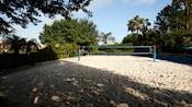 Uma quadra de vôlei de areias brancas com rede azul