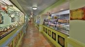 Un pasillo con terrarios y un exhibidor repleto de comida envasada y un cartel que dice Picabu Greens