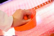 Primer plano de una mano que sostiene un mazo de hockey de mesa color naranja sobre una mesa