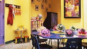 A kid's play room with craft table, toys and a big-screen TV