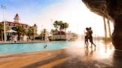 Joven pareja, parada detrás de una cascada, saludan a sus 2 hijos en la piscina