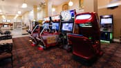 A row of video games such as Guitar Hero and NASCAR Racing in a section of a cavernous room