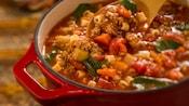Una cuchara de madera revolviendo sopa minestrone en una olla