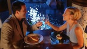A man and a woman toast their glasses together at a table plated with food